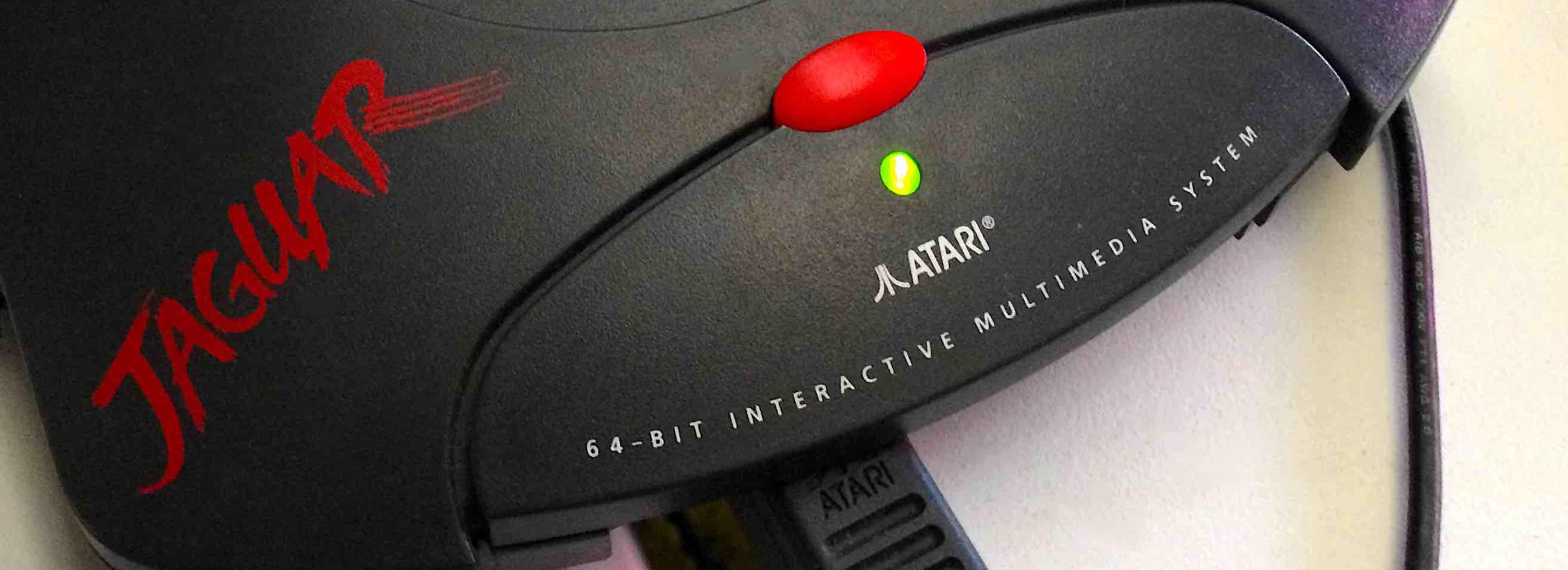"""Zdjęcie przedstawiające zbliżenie naprzód konsoli Atari Jaguar. Widać nanim czerwoną nazwę Jaguar, białe logo Atari oraznapis: """"64 bit interactive multimedia system""""."""